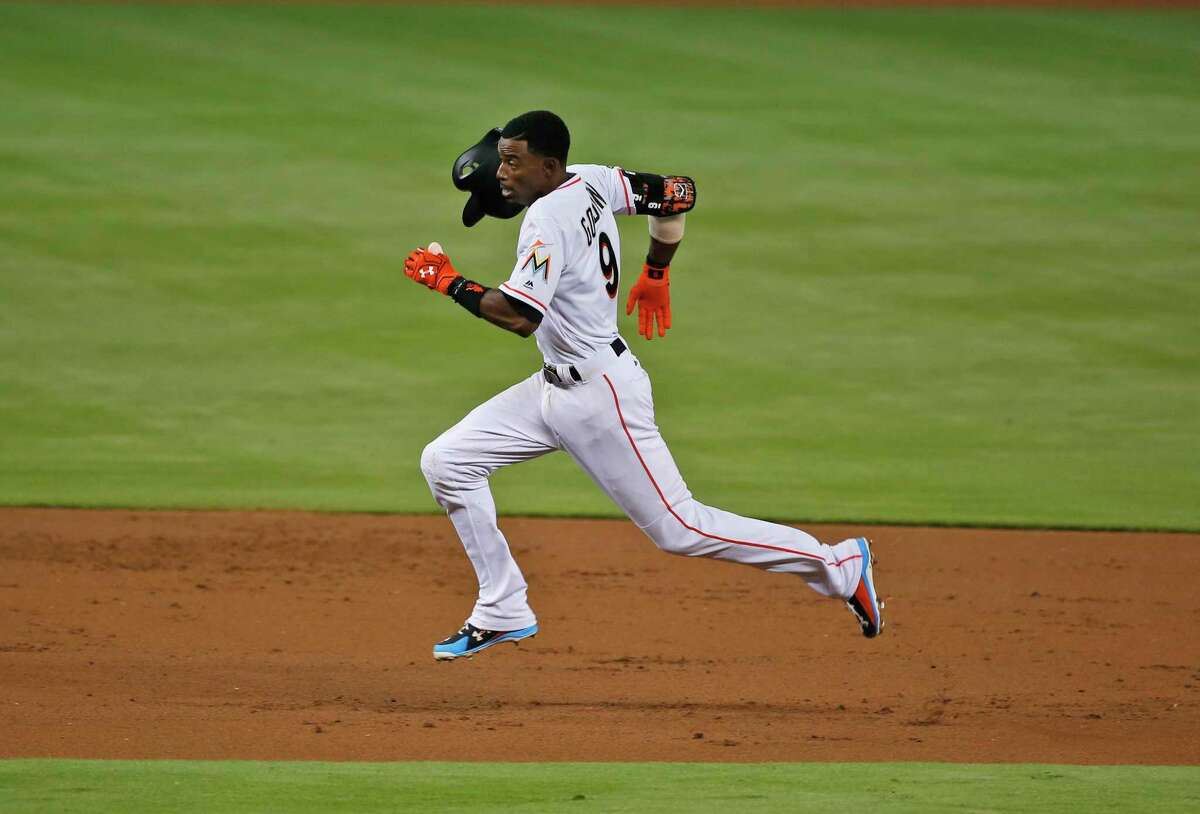 Miami Marlins' Dee Gordon heads to third base on a throwing error by Houston Astros starting pitcher Dallas Keuchel during the first inning of a baseball game, Tuesday, May 16, 2017, in Miami. (AP Photo/Wilfredo Lee)