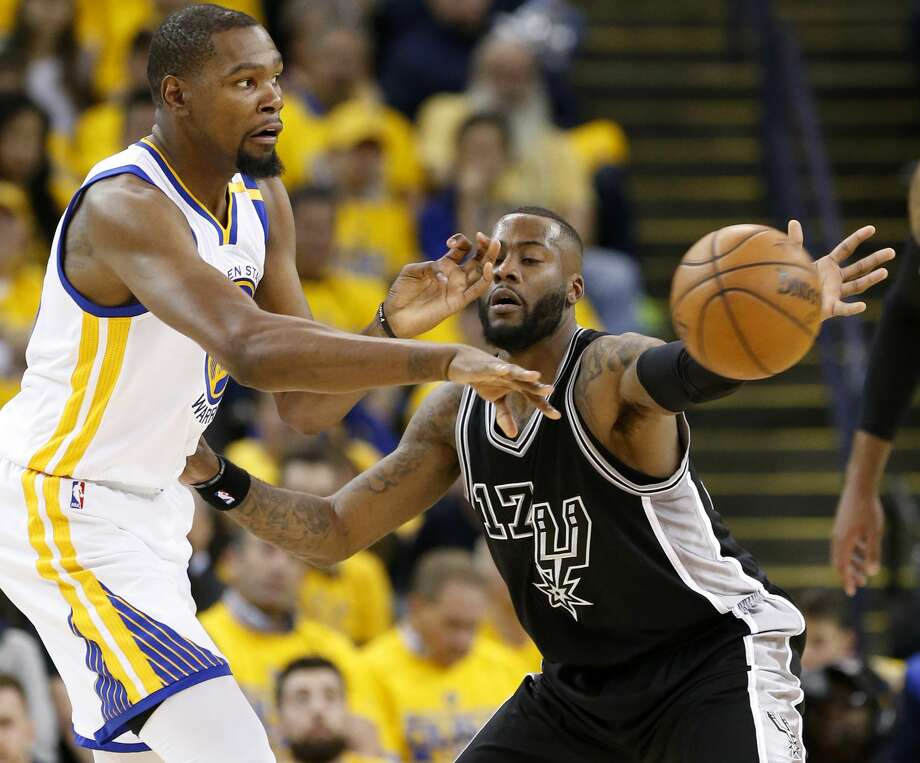 Golden State Warriors' Kevin Durant passes around San Antonio Spurs' Jonathon Simmons during first half action in Game 2 of the Western Conference Finals held Tuesday May 16, 2017 at Oracle Arena in Oakland, CA. Photo: Edward A. Ornelas/San Antonio Express-News