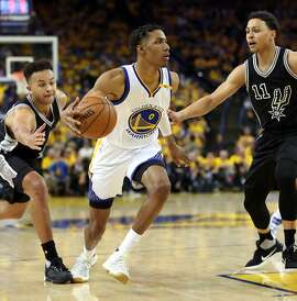 Golden State Warriors' Patrick McCaw drives between San Antonio Spurs' Bryn Forbes (11) and Kyle Anderson in 4th quarter during Warriors' 136-100 win in Game 2 of NBA Western Conference Finals in Oakland, Calif., on Tuesday, May 16, 2017.