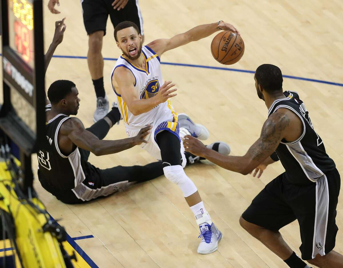Golden State Warriors' Stephen Curry is fouled by San Antonio Spurs' Dewayne Dedmon as he scores in 3rd quarter of Warriors' 136-100 win in Game 2 of NBA Western Conference Finals in Oakland, Calif., on Tuesday, May 16, 2017.