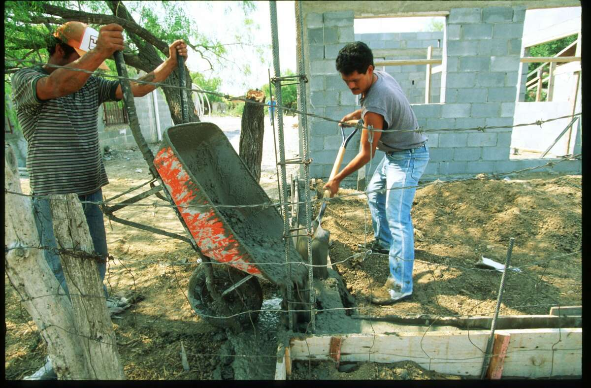 A man pours cement to build the foundation for his home in Colosio colonias April, 1996 in Nuevo Laredo, Mexico. The colonias have virtually no medical facilities and exhibit a variety of economic levels since new arrivals live in shacks and workers of the maquiladoras live in one or two story cinder block homes. (Photo by Paul S. Howell/Liaison)