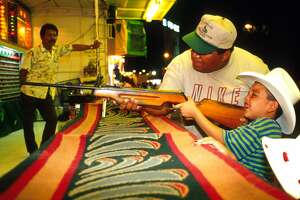 394003 04: An unidentified man helps his son at an arcade game at a fairground September 16, 1999 in Nuevo Laredo, Mexico during Independence Day festivities. (Photo by Per-Anders Pettersson/ Getty Images)