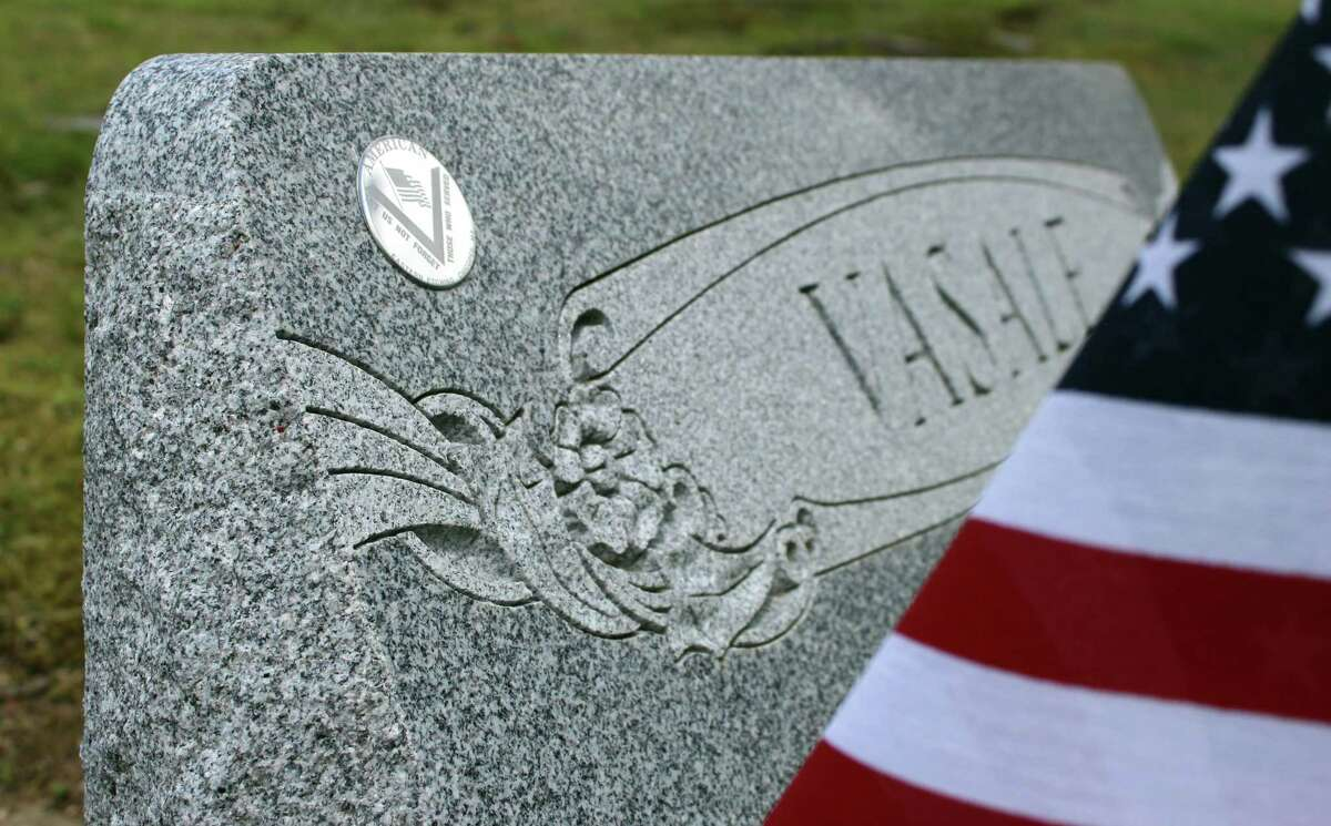 """American Legion Post 86 member Bing Ventres made shiny emblem stickers to make it easier to identify veterans' graves. The emblem reads, """"Let us not forget those who served."""""""