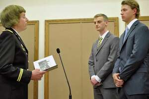 Maj. Nancy Bates (left) presents West Point Academy appointments to Joseph Waldron and Michael Halas.