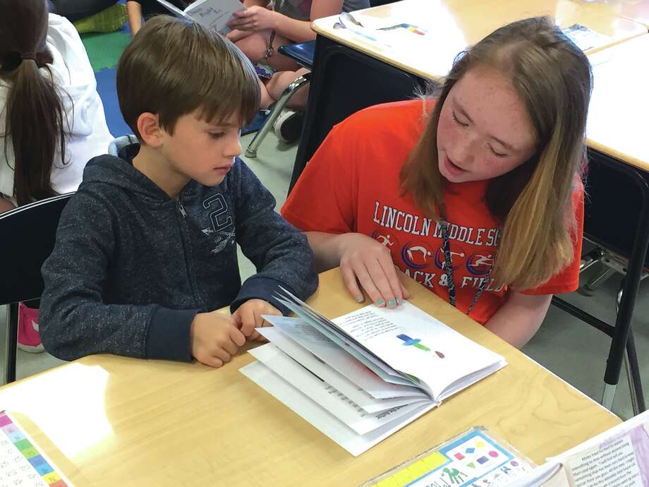 Leclaire Elementary studente Michael McNamara listens as Lindsey Lankford, of Lincoln Middle School, reads the book she wrote for first- and seventh-grade project. Photo: Julia Biggs • Intelligencer