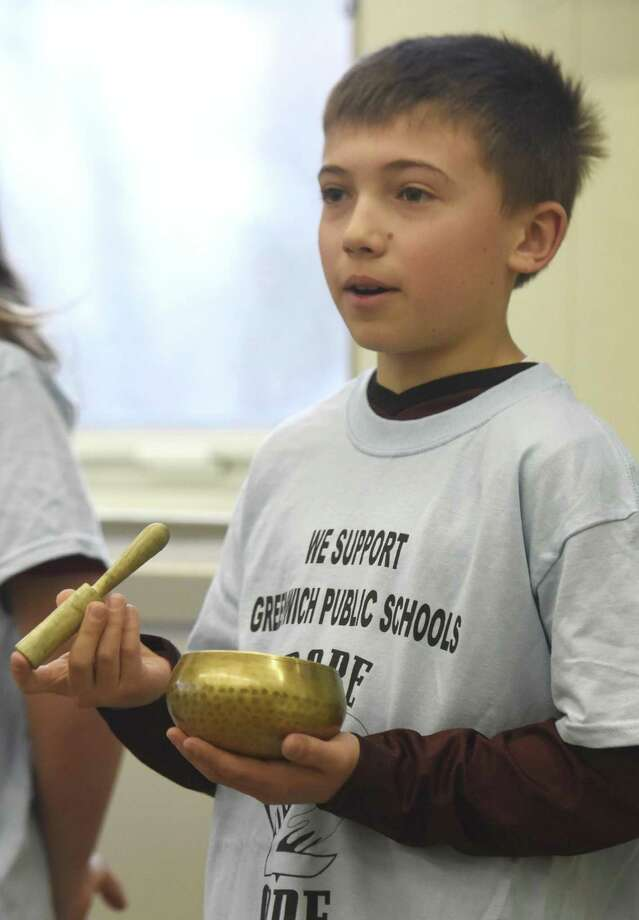 Julian Curtiss fifth-grader Jake Tisler makes a ringing noise with a bell after a period of reflection during a mindfulness presentation to Greenwich first responders at the Board of Education in Greenwich, Conn. Thursday, April 6, 2017. Representatives from the Greenwich police, fire and EMS services learned about mindfulness and stress-management strategies that can be helpful in their day-to-day work. Photo: Tyler Sizemore / Hearst Connecticut Media / Greenwich Time