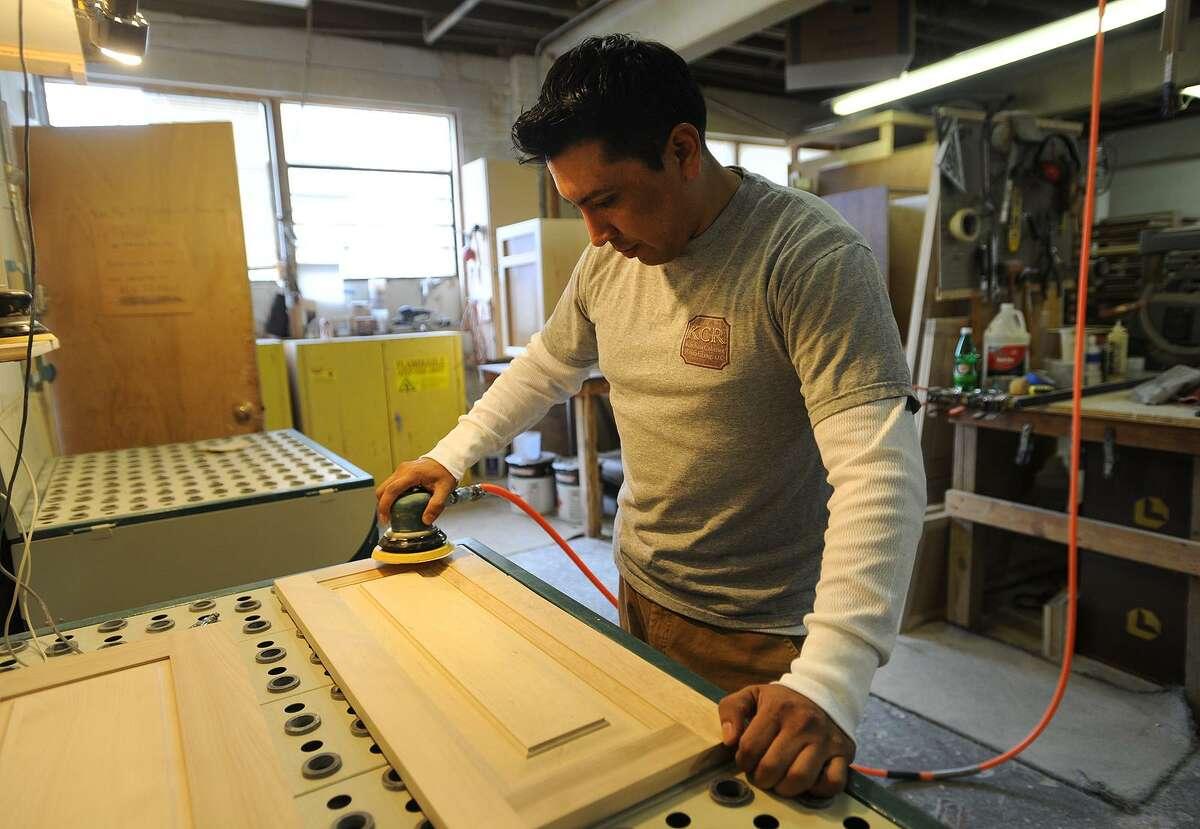Carlos Valdiviezo sands cabinet doors at Kitchen Cabinet Resurfacing Inc.'s shop in Bridgeport.