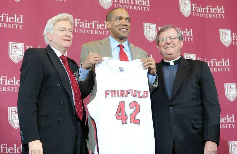 Fairfield University Director of Athletics Eugene Doris, left, in a 2011 photo with basketball coach Sydney Johnson (center) and then-univeristy President The Rev. Jeffrey P. von Arx. Photo: Autumn Driscoll / ST / Connecticut Post