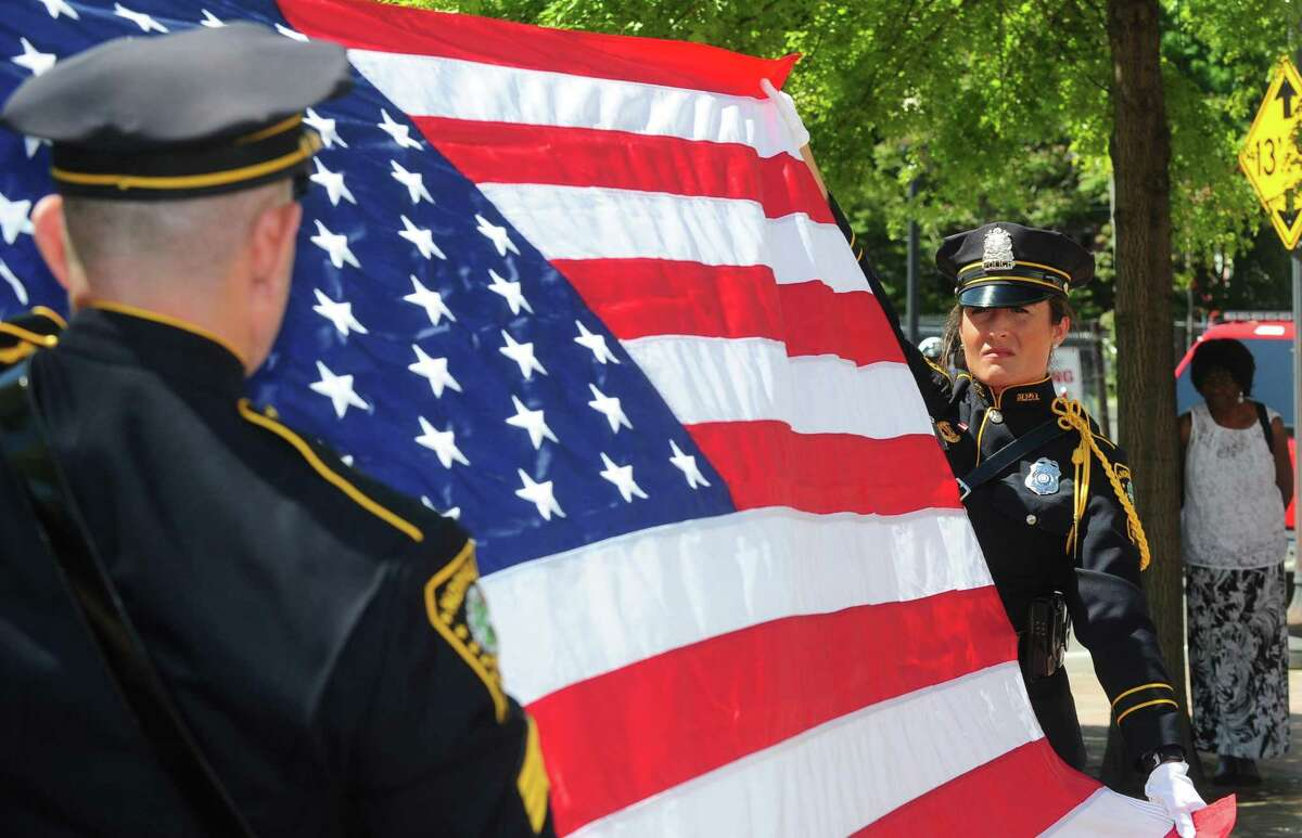 Norwalk police Sergeant Joseph Moquin and Officer Cristina Capela retire the flag as dignitaries, and other local police departments take part in the annual police memorial at police headquarters in honor of National Police Week Wednesday, May 17, 2017, in Norwalk, Conn.