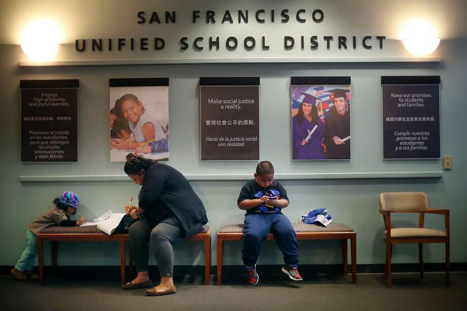 In this 2015 file photo, Carolina Rodas fills out a San Francisco Unified School District application for her son Maifala Rodas (right) as niece Camila Rodas (left), draws next to her. Photo: Lea Suzuki, The Chronicle
