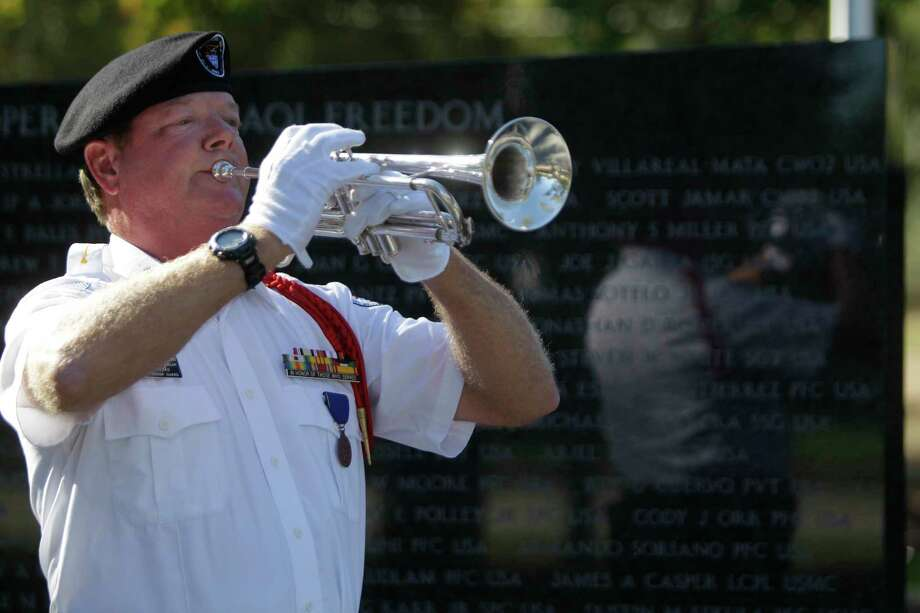 FOR VETERANS DAY  Buglar Benjamin Brooks plays Taps as members of the National Memorial Ladies and others pay respects to fallen U.S. Army Staff Sgt. Kashif M. Memon at the Fallen Warriors Memorial at Cy-Champ Park, 14107 Cutten Road, Friday, Nov. 9, 2012, in Houston. The brief ceremony was held to coincide with time of the funeral service for U.S. Army Staff Sgt. Kashif M. Memon. The Fallen Warriors Memorial honors Texas soldiers killed in action in Iraq and Afghanistan.   ( Melissa Phillip / Houston Chronicle ) Photo: Melissa Phillip, Staff / © 2012 Houston Chronicle
