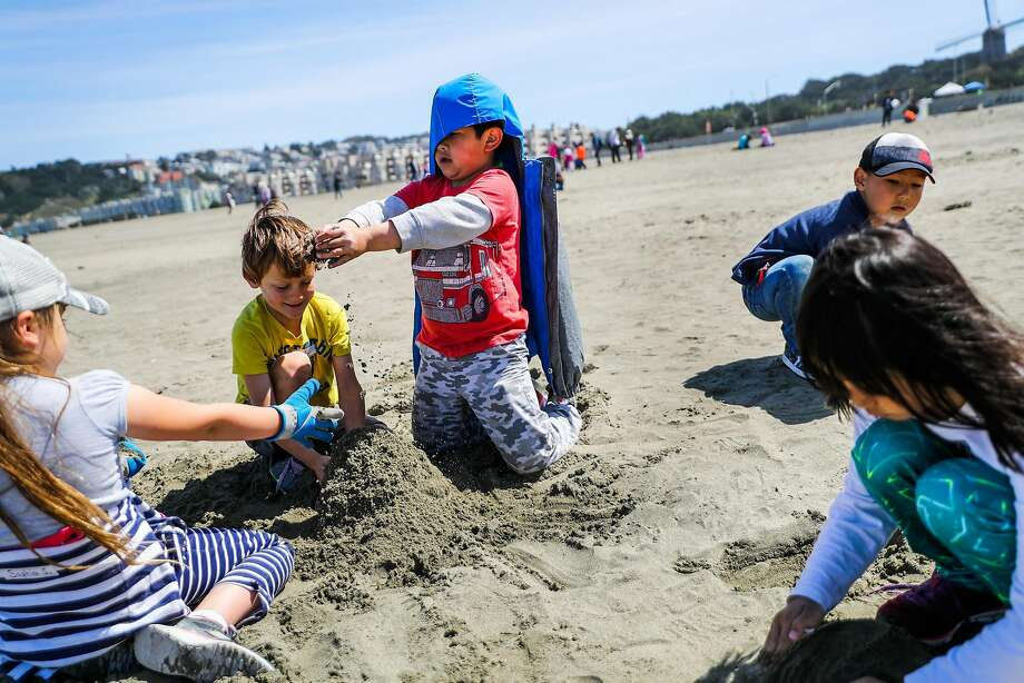 (l-r) Students Sophia S.,8, Woody S.,8, and Anson A., 7, play in the sand while participating in the 24th annual Kids Ocean Day Adopt -A-Beach Cleanup at Ocean Beach in San Francisco, California, on Wednesday, May 17, 2017. Photo: Gabrielle Lurie, The Chronicle