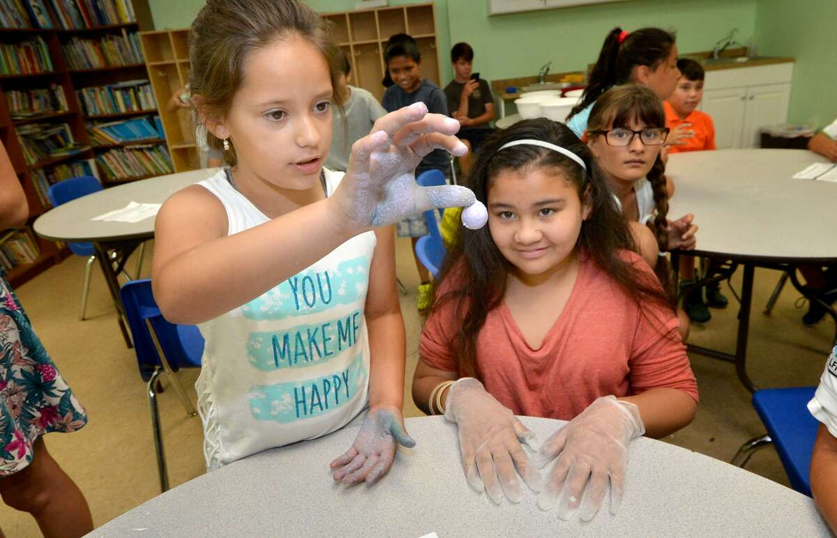 Lucia Corona, 10, shows her bouncing ball of of polymer to Meanjaliz Merino during a science program at the Connecticut Yankee Council's Summer STEM Camp at the South Norwalk Community Center in July 2016.