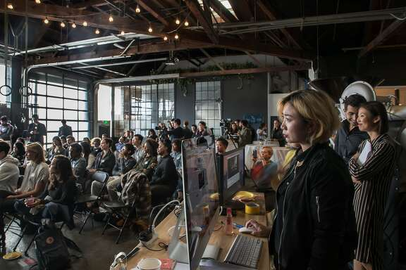 Theresa Phung, Wefunder's Chief Storyteller, along with Omar Shammas and Jiwon Moon, also of the company, watch two companies make their pitches at an event held at Red Bay Coffee on Wednesday, May 17, 2017 in Oakland, Calif.   Moon said about 125 people attended the event.