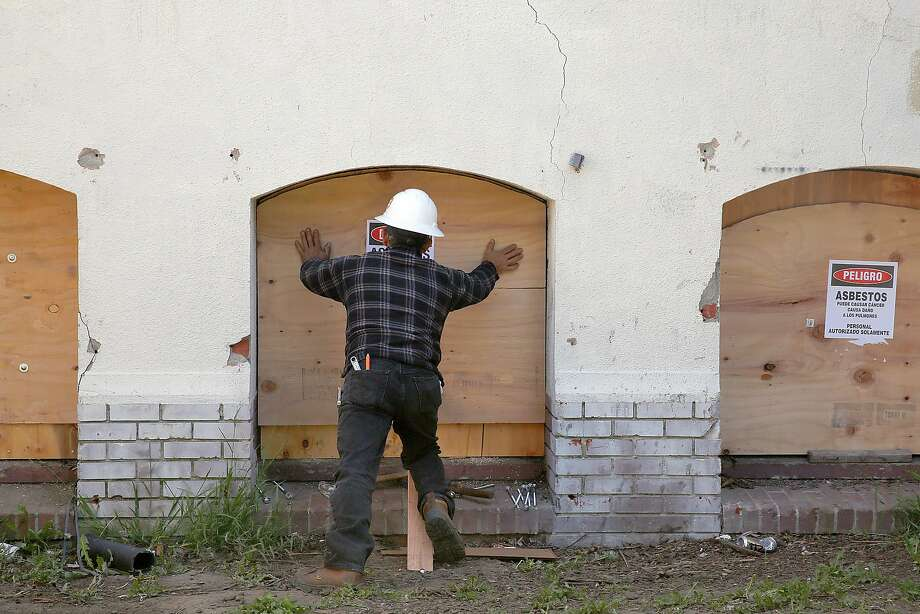 Basement windows are boarded up at the officially vacant city-owned building on Miller Avenue in Oakland. Photo: Liz Hafalia, The Chronicle