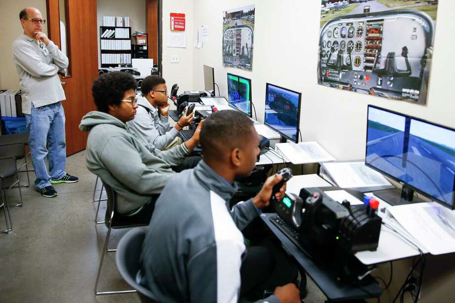 Former Houston Rockets head coach and Pro-Vision Charter School board member Jeff Van Gundy, left, watches students practice on flight simulators during a tour of the school Thursday, March 2, 2017 in Houston. Photo: Michael Ciaglo, Houston Chronicle / Michael Ciaglo