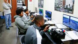 Former Houston Rockets head coach and Pro-Vision Charter School board member Jeff Van Gundy, left, watches students practice on flight simulators during a tour of the school Thursday, March 2, 2017 in Houston.