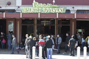 Tourists walk past Ripley's Haunted Adventure, a year-round haunted house located in Alamo Plaza.