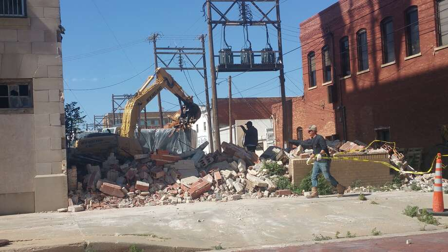 Alonzo Castillo, an employee of Hastey Construction, uses a water hose to help settle dust as the old Union Bus Depot is demolished late Wednesday afternoon. That work is a preliminary step in the restoration of Plainview's Hilton Hotel, which will become the Conrad Lofts. The Hilton Hotel opened prior to the onset of the Great Depression in 1929. The bus station was added later, and eventually became home to a private club, named The Desert Inn, which has been closed since the mid-1980s.