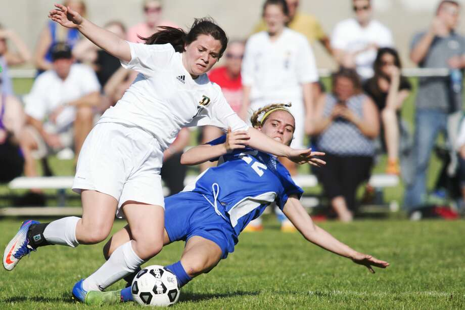 Midland's Makenzie Rajewski slide tackles Dow's Elizabeth Green in a game at Dow High School on Wednesday. Photo: Theophil Syslo