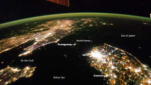 If not for labels, this image might appear to show a wide straight connecting the Sea of Japan and the Yellow Sea between China and South Korea. But looking closely, you can see that big dark area is just North Korea, apparently all but completely shut down at night. You can also make out the orange lights along the border of the demilitarized zone as light turns to dark in the image. NASA photo.