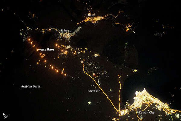 Lights often show the starkness of borders at night. In this image from the International Space Station, Kuwait City's populated borders are brightly lit in the lower righthand corner. To the left, a string of gas flares can be seen burning as well. NASA photo.