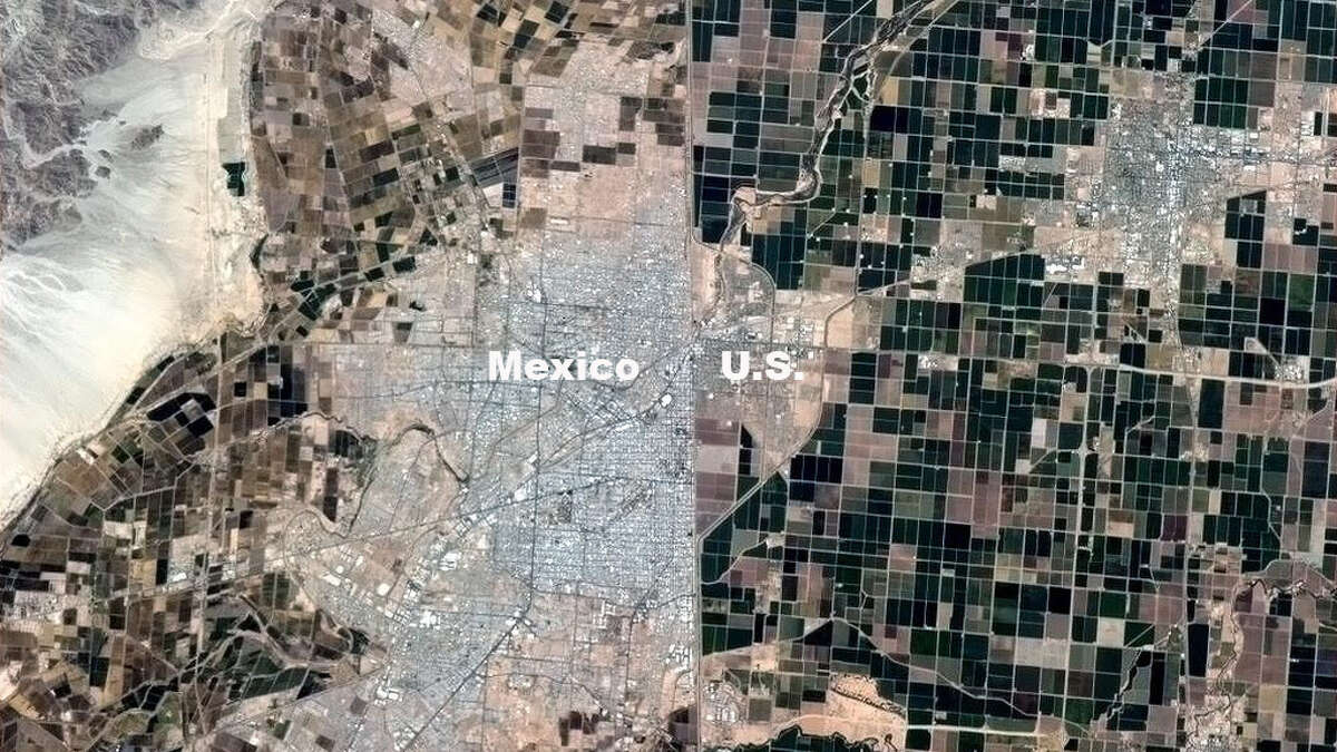 The lush farmlands of California (on the right, or northern side) stand in stark contrast to the browner farmlands surround Mexicali, just across the southern border (to the left) in Mexico.