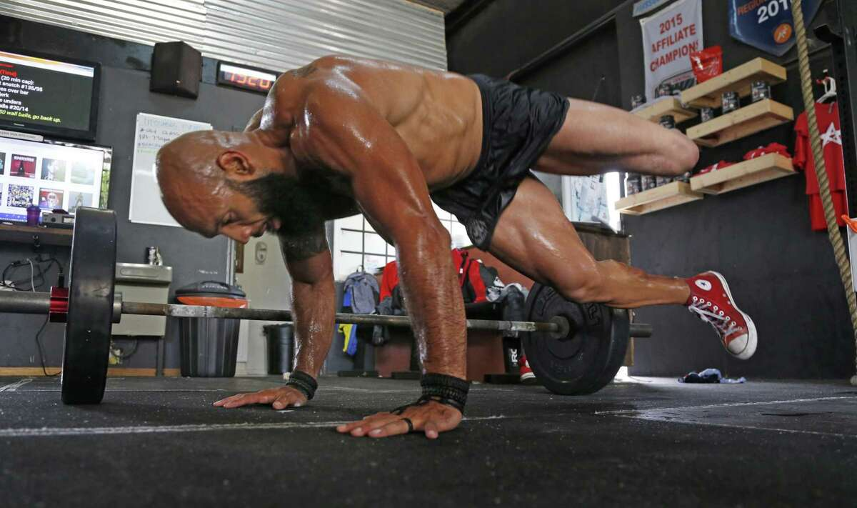 Jose Sanchez hurdles over weights after he took off his artificial leg. Jose Sanchez, Marine and Boston Marathon runner from San Antonio will be working out today with two Boston Marathon Runnerson Thursday, May 11,2017 at Lone Star Crossfit.