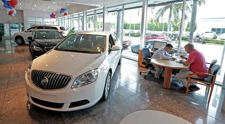 Felipe Perdomo, left, closes a deal with customer John Tsialas at a GMC Buick dealership in Miami. Auto loans are considered part of household debt.  Photo: Alan Diaz, STF / Copyright 2017 The Associated Press. All rights reserved.