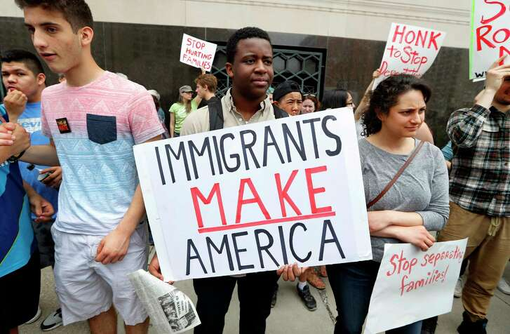 FILE - In this Tuesday, May 16, 2017, file photo, Torianto Johnson, a freshman at Pioneer High School in Ann Arbor, holds a sign supporting immigrants during a rally outside a federal courthouse in Detroit. Protesters rallied in hopes public outcry will again delay the deportation of Jose Luis Sanchez-Ronquillo from the United States to Mexico. U.S. immigration arrests increased nearly 40 percent in early 2017 as newly emboldened agents under President Donald Trump detained more than 40,000 people suspected of being in the country illegally, with a renewed focus on immigrants without criminal convictions. (AP Photo/Paul Sancya, File)