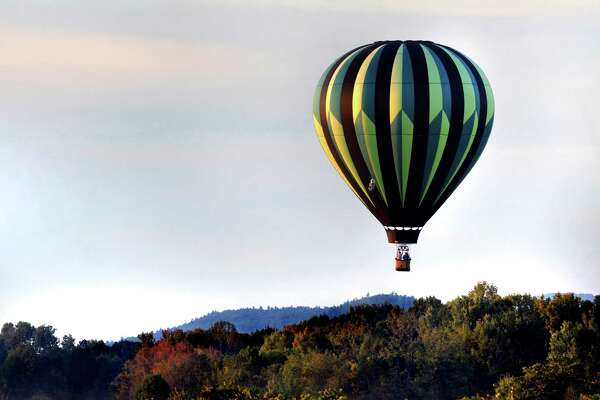 A hot air balloon flies over the landscape during the Adirondack Balloon Festival on Friday, Sept. 18, 2015, at Floyd Bennett Memorial Airport in Queensbury, N.Y. Flight times are 6:30 a.m. and 5 p.m. on Saturday and Sunday.(Cindy Schultz / Times Union)