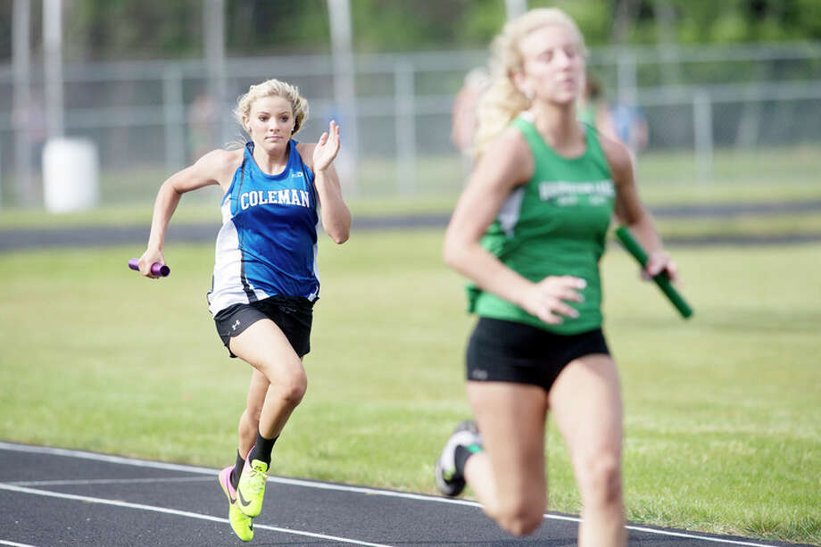 BRITTNEY LOHMILLER | blohmiller@mdn.net Coleman's Makailyn Monson, left, closes the gap between her and Houghton Lake's Bridget Ripke during the last leg of the 4x100 relay during a Wednesday afternoon track meet. / Midland Daily News