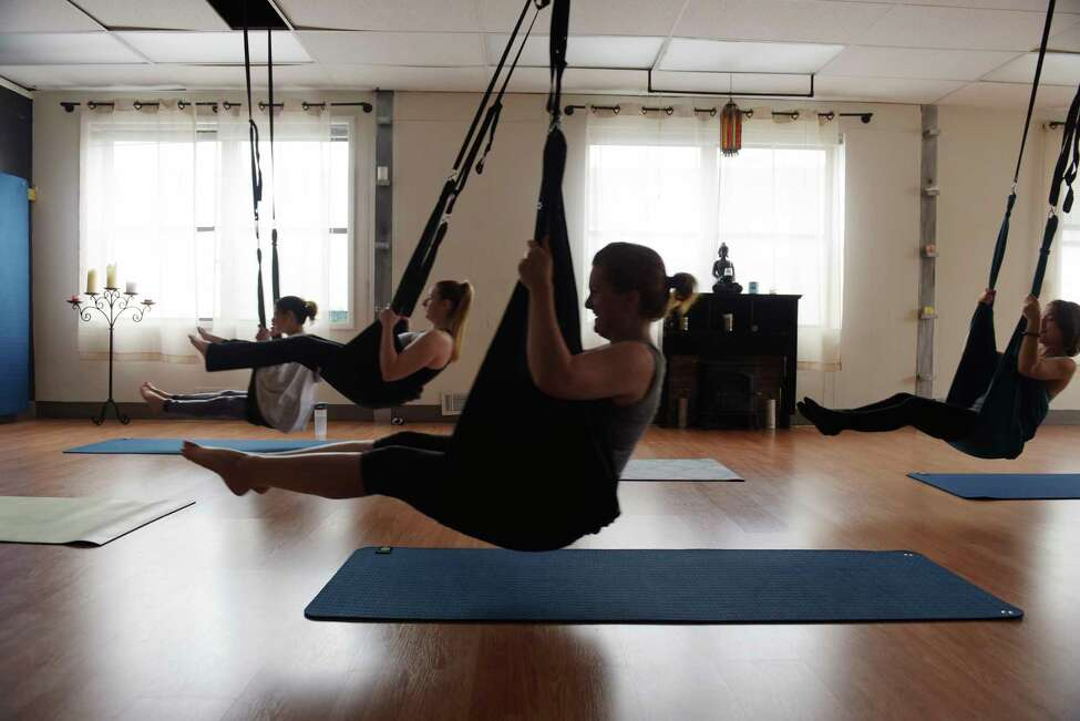 Times Union reporter Leigh Hornbeck, center, takes part in an aerial yoga class at the Good Karma Studio on Tuesday, April 25, 2017, in Albany, N.Y. (Paul Buckowski / Times Union)