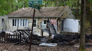 The smoldering remains of a building at 29 Cold Spring Avenue on Monday, May 15, 2017, in Schodack, N.Y. Authorities said someone set fire to the structure on Sunday and the fire is considered a hate crime. Schodack police do not identify the race or religion of the homeowners but a source says the victims are black. (Will Waldron/Times Union)