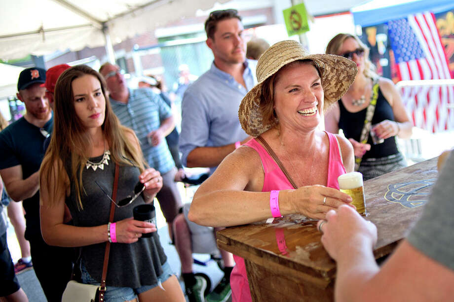 Liz Seelhoff smiles while being served a beer during Tapped in this 2016 file photo. / Midland Daily News