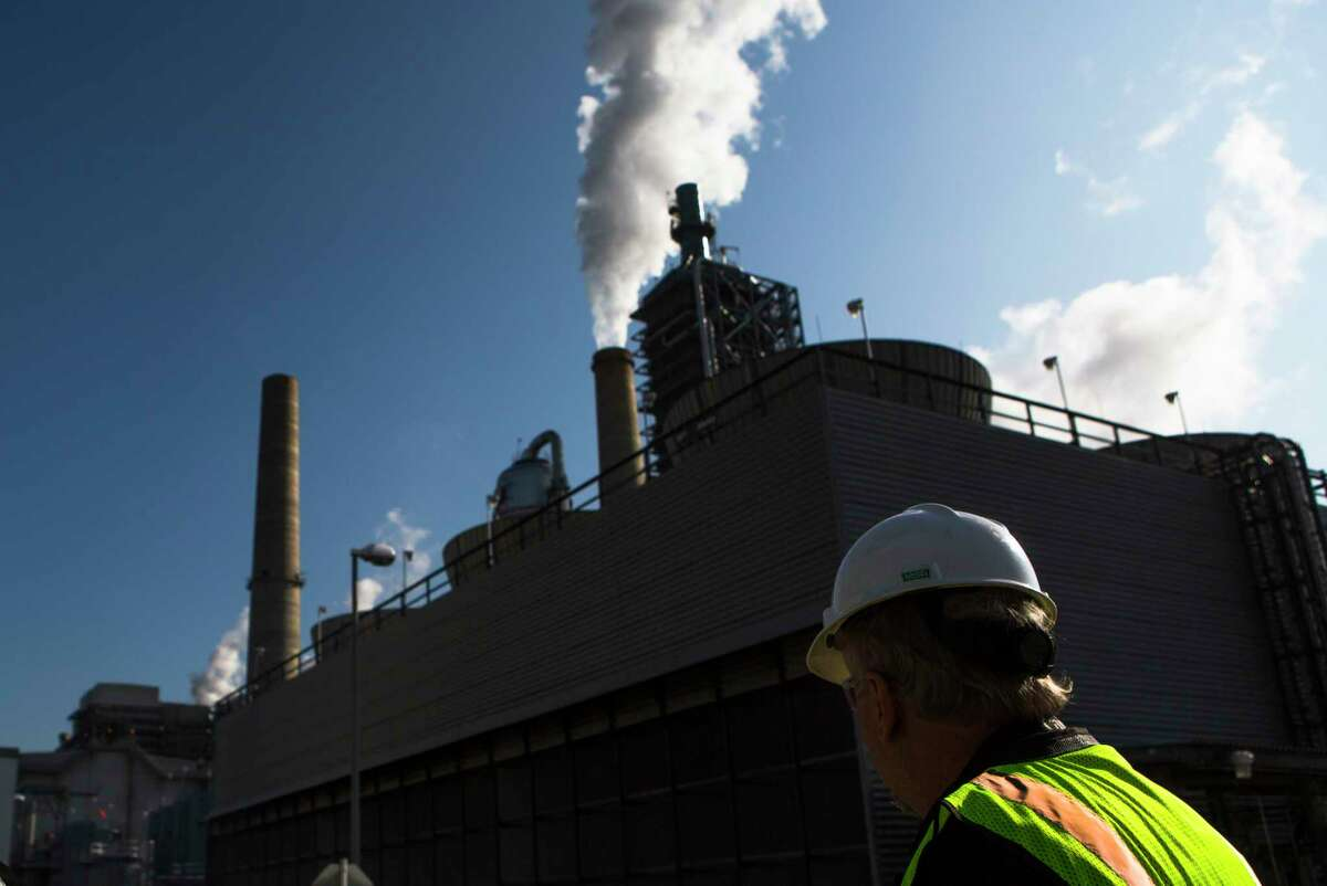 David Knox from NGR makes walks by a cooling tower silhouetted, Tuesday, Dec. 20, 2016, in For Bend County. NGR Energy and JX Nippon Oil & Gas Exploration Corporation have built the Petra Nova Carbon Capture Project. The project is a commercial-scale carbon capture system that captures carbon dioxide in the processed flue gas from an existing unit at the WA Parish power plant. ( Marie D. De Jesus / Houston Chronicle )