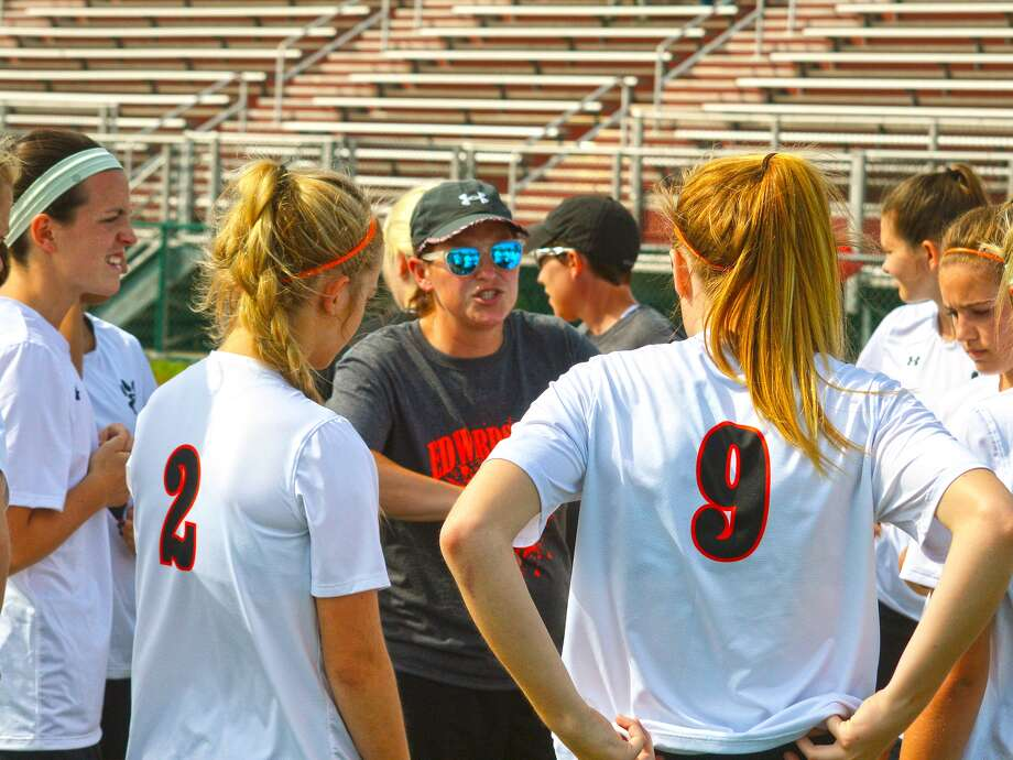 Edwardsville girls' soccer coach Abby Comerford, center, talks to her team before the Class 3A Belleville West Regional opener against O'Fallon on Monday.