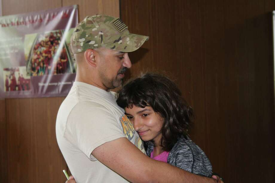 Army Staff Sgt. Michael Bichon hugs his daughter, Hilda, an eighth-grader at Tarkington Middle School, on Wednesday, May 10. Michael has been away for a year in South Korea. Photo: Vanesa Brashier / Vanesa Brashier