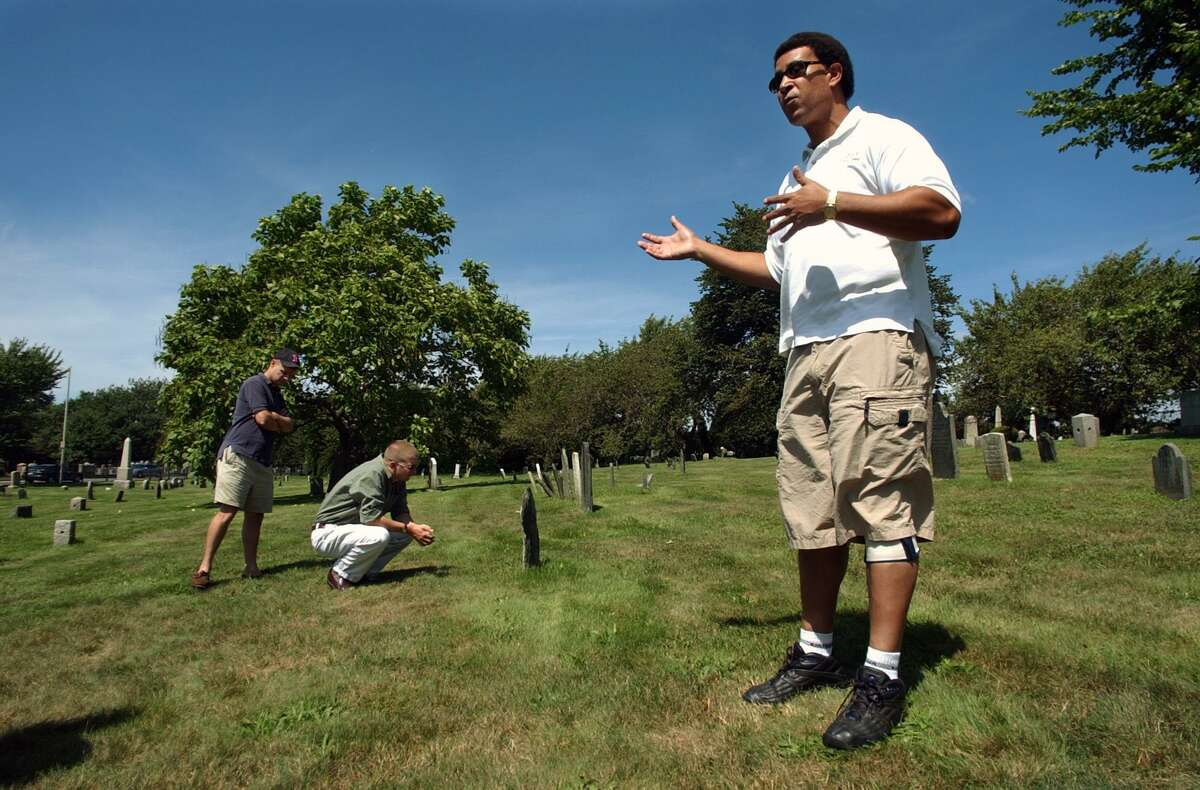 Historian Keith Stokes, right, executive director of the Newport County Chamber of Commerce, gestures as he speaks to a small informal gathering of local officials touring the Common Burying Ground Tuesday, Aug. 24, 2004, in Newport, R.I., as a slate headstone dating to 1772 sits on the side. (AP Photo/Victoria Arocho)