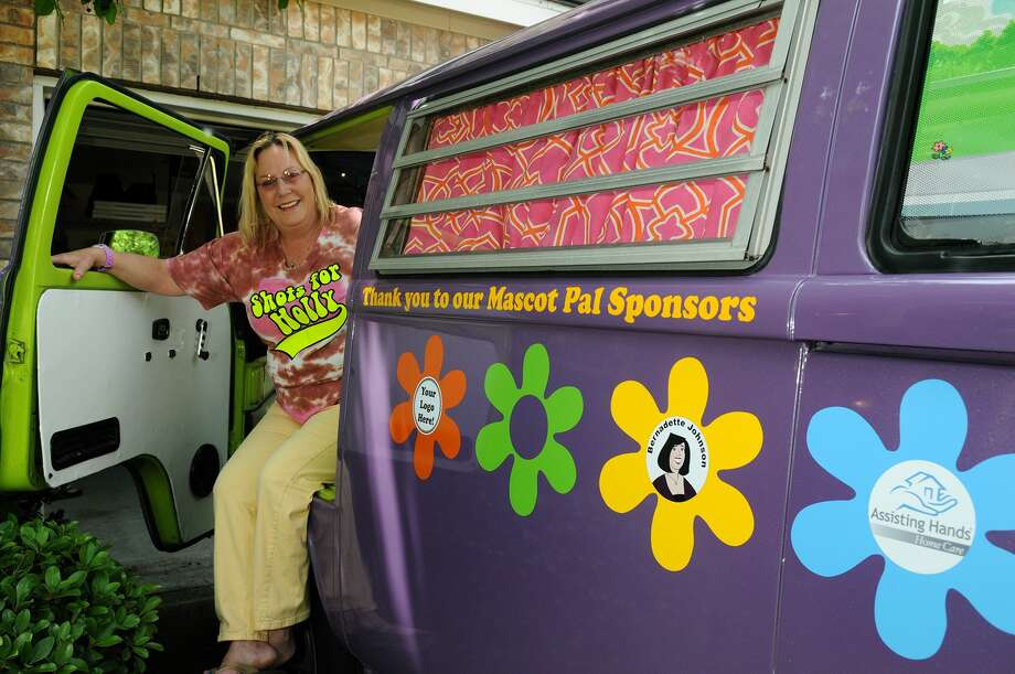 Michelle Becker, the founder of nonprofit Shots for Holly, poses with her mascot VW bus, complete with headlight eyelashes, at her home in Cypress. Photo: Jerry Baker, Freelance