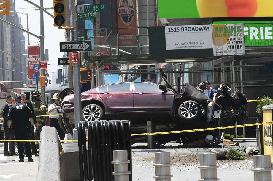 A car rests on a security barrier in Times Square after it was driven into a crowd of pedestri ans. The driver, a Navy veteran, was cited for drunken driving in 2008 and 2015, officials say. Photo: Mary Altaffer, Associated Press