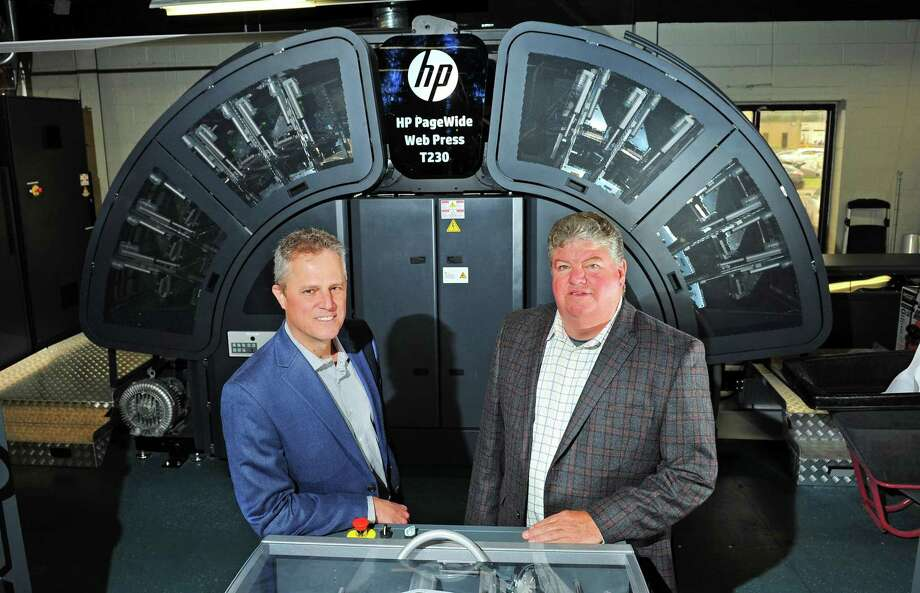Premier Graphics COO Cesar Garcia, left, and CEO and President Tim Cicchese pose with a new HP Web Press T230 inside the facility at 860 Honeyspot Road in Stratford, Conn., on Tuesday May 16, 2017. Photo: Christian Abraham / Hearst Connecticut Media / Connecticut Post