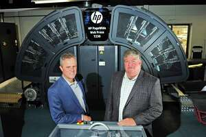 Premier Graphics COO Cesar Garcia, left, and CEO and President Tim Cicchese pose with a new HP Web Press T230 inside the facility at 860 Honeyspot Road in Stratford, Conn., on Tuesday May 16, 2017.