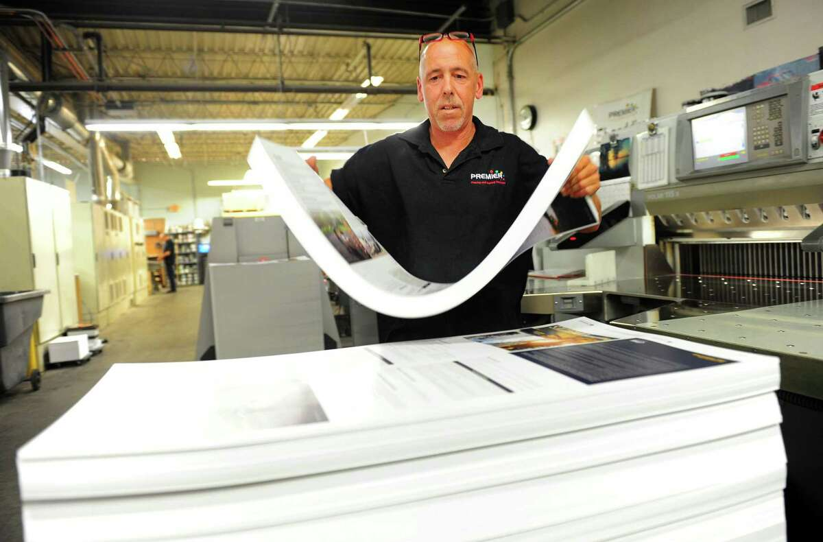 Premier Graphics Patrick McNamara places a stack of printed sheets onto a pile after trimming off the edges with a cutting machine during his shift at the facility at 860 Honeyspot Road in Stratford, Conn., on Tuesday May 16, 2017.