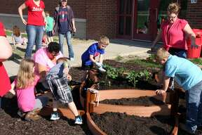 First graders at Unionville-Sebewaing Area Elementary School planted a raised garden Thursday morning with supplies donated by Gleaner Life Insurance Society, USA Arbor of Sebewaing.