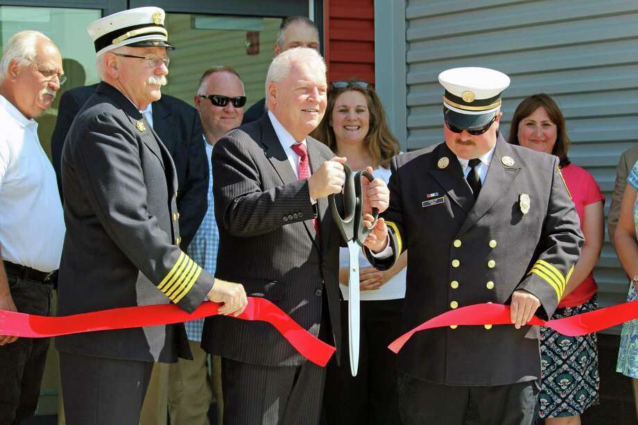 Fire Chief Denis McCarthy, First Selectman Mike Tetreau, and Asstant Chief Scott Bisson cut the red ribbon to officially mark the opening of a new regional fire training center in Fairfield. Photo: Genevieve Reilly / Hearst Connecticut Media / Fairfield Citizen