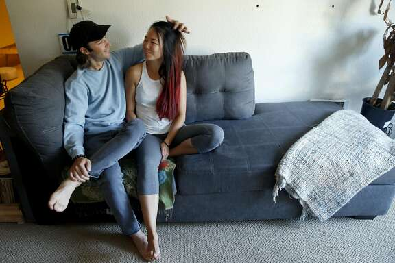 Jered Snyder and his wife Jen Zhao relax on the couch in their apartment in Oakland, Calif. on Thursday, May 18, 2017. Snyder and Zhao, who married in 2015, are among a growing trend of interracial couples.