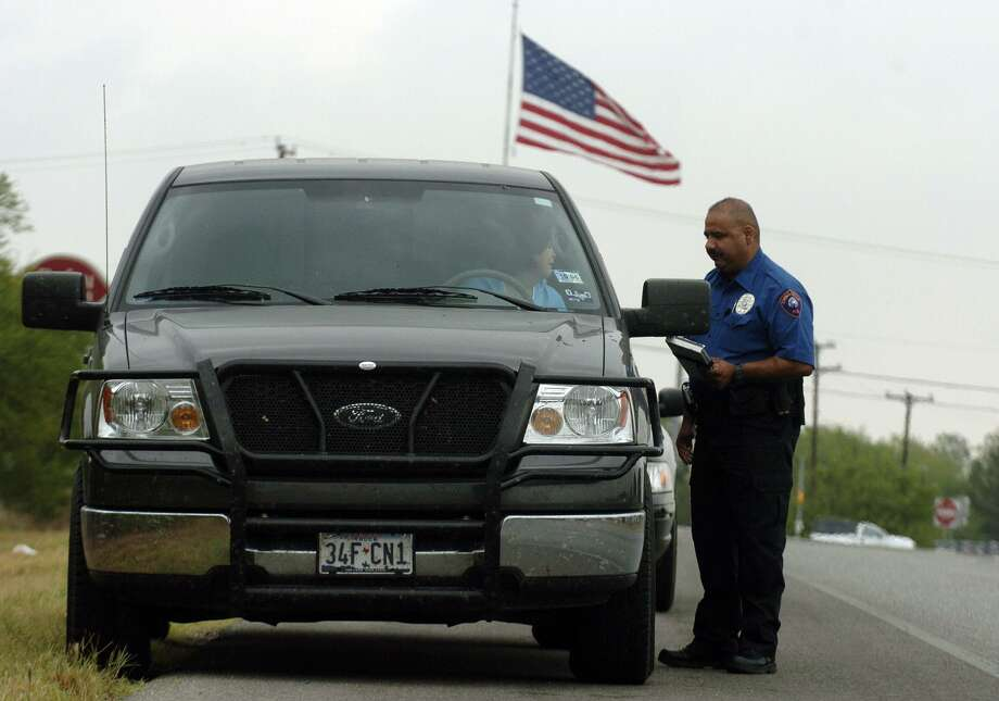 A China Grove police officer warns a motorist on highway 87 to slow down in 2006. If you get a ticket and can pay, you're fine, but if you're poor, that ticket can spiral into big debt — and no license. Photo: JOHN DAVENPORT /SAN ANTONIO EXPRESS-NEWS / SAN ANTONIO EXPRESS-NEWS