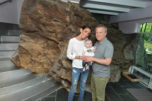 Dori and Elli Levy with daughter Harlow at the entryway to their North Seir Hill Road home alongside a boulder that is part of the outside and inside of the house in Norwalk.