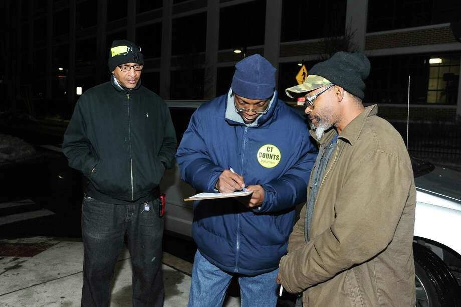 Volunteers Leroy Jordan (center) and Vertiz Waters (left) fills out a survey with Keith Thompson's (right) information to help document those in need in Stamford in the South End on Tuesday, Jan. 26, 2016. The annual Point in Time survey, of which Jordan and Waters are volunteers for, is a physical count of homeless persons which takes place in communities across the country. Photo: Michael Cummo / Hearst Connecticut Media / Stamford Advocate